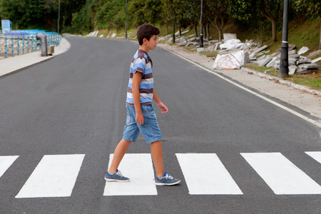 Photo for Teenager through a zebra crossing in his town - Royalty Free Image