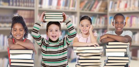 Foto de Four children in the library with many books - Imagen libre de derechos