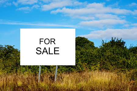 Foto de Cartel advertising For Sale. Business of buying and selling land - Imagen libre de derechos
