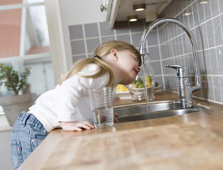 Foto de Small Girl in the kitchen drinking water - Imagen libre de derechos