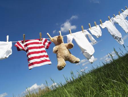 Photo pour Baby Clothing and a teddybear on a clothesline towards blue sky - image libre de droit