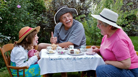 Grandparents and 6 year old granddaughter sit at a small table in a garden, having a tea party and making funny faces at each other. Straw hats, china tea cups, cupcakes, and embroidered tablecloth are accessories. Horizontal format.