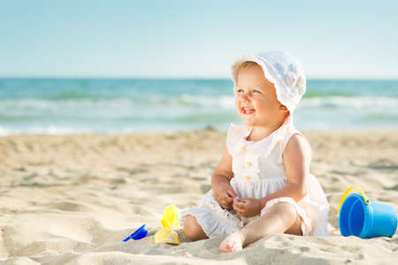 Photo pour Baby playing on the sandy beach near the sea - image libre de droit