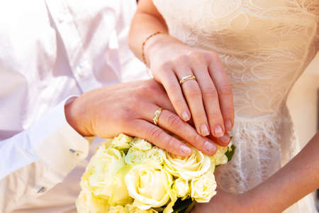 Photo for Hands and rings on wedding bouquet close up - Royalty Free Image