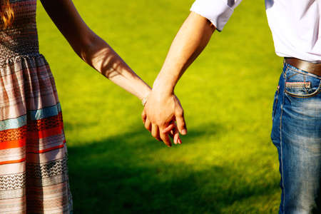 Photo for Couple holding hands on the background of green grass - Royalty Free Image