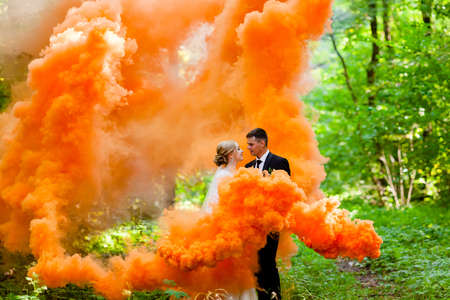 Photo for The bride and groom with the orange colored smoke at the background of summer forest - Royalty Free Image