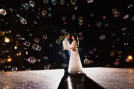 Photo for Couple of newlyweds and huge amount of bubbles are flying in the air - Royalty Free Image