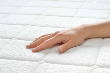 Photo pour Choosing mattress and bed. Close-up of female hand touching and testing mattress in a store. Copy space. - image libre de droit
