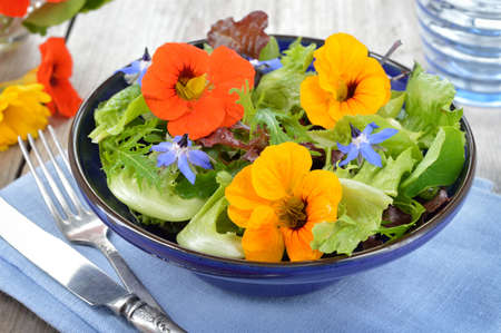 Photo for Fresh summer salad with edible flowers nasturtium, borage flowers in a bowl. - Royalty Free Image
