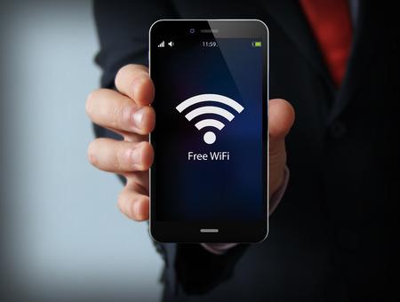 Foto de business and mobility communications concept: businessman holding a modern smartphone with free wifi zone icon - Imagen libre de derechos