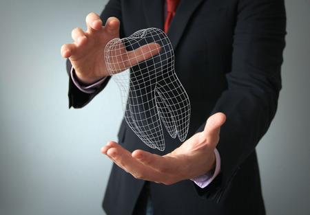 Foto de dental implant design concept: 3d tooth wire on a businessman hands - Imagen libre de derechos