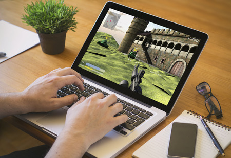 Photo pour Businessman at work procrastinating. Close-up top view of man working on laptop with videogame. all screen graphics are made up. - image libre de droit