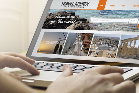 Foto de online travel concept: man using a laptop with travel agency on the screen. Screen graphics are made up. - Imagen libre de derechos