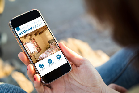 Foto de close-up view of young woman holding a smartphone with booking room app on screen. All screen graphics are made up. - Imagen libre de derechos