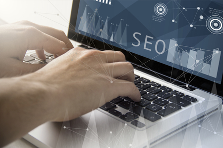 Foto de technology and business concept: man using a laptop with seo software on the screen. All screen graphics are made up. - Imagen libre de derechos