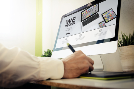 Foto de web developer designing a responsive website. All screen graphics are made up. - Imagen libre de derechos