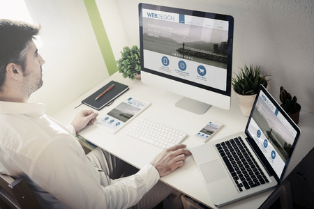 Foto de man working with devices with responsive web design. All screen graphics are made up. - Imagen libre de derechos