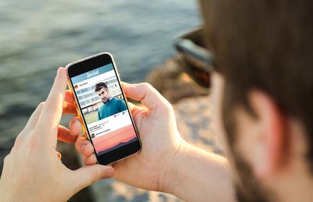 Foto de man on the coast using his smartphone. All screen graphics are made up. - Imagen libre de derechos