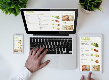 Foto de office tabletop with tablet, smartphone and laptop showing cool responsive online supermarket website - Imagen libre de derechos