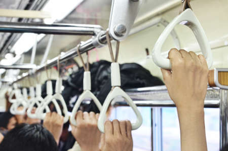 Foto per Passengers hands holding handrails in commuter line - Immagine Royalty Free