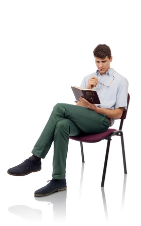 Young christian man sitting and reading Holy Bible