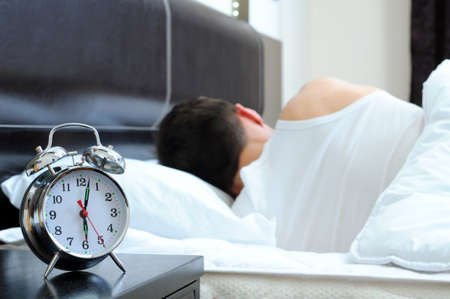 Photo pour Man sleeping with alarm clock in foreground - image libre de droit