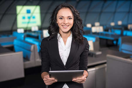 Photo pour Portrait of a smiling young woman with tablet is standing in the background of the modern conference hall. - image libre de droit