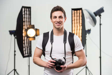Photo for Young smiling photographer with camera in professionally equipped studio. - Royalty Free Image