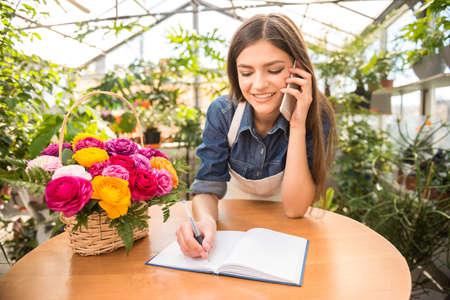 Photo pour Portrait of young female florist talking on phone and making notes at flower shop. - image libre de droit