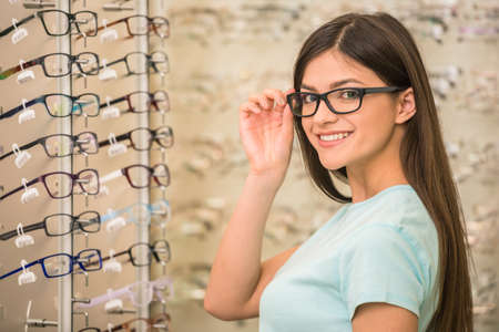 Foto de Young woman is choosing a glasses in optician store. - Imagen libre de derechos