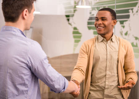 Foto de Smiling businessman handshaking with his colleague. Back view. - Imagen libre de derechos