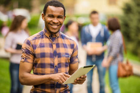 Photo for Young attractive smiling mulatto student  using tablet outdoorsca on campus at the university. - Royalty Free Image