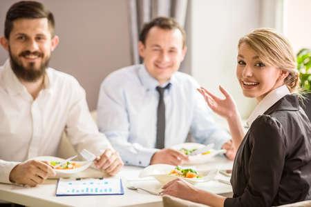 Foto de Beautiful businesswoman in suit talking with partners at business lunch. - Imagen libre de derechos