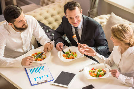 Photo pour Business people in formalwear discussing something during business lunch. - image libre de droit