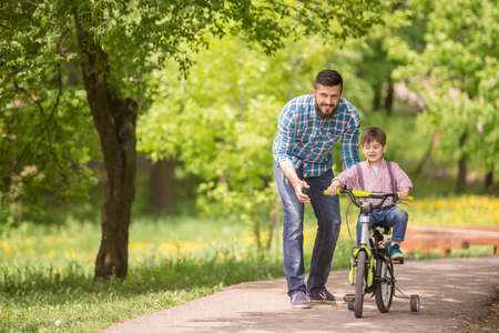 Photo pour Young father teaching son to ride bicycle in summer park. - image libre de droit