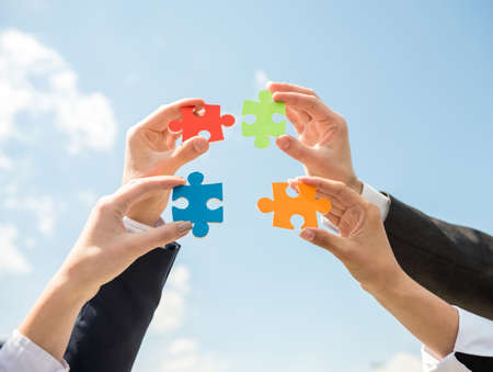 Photo pour Closeup of business people wanting to put four pieces of puzzle together. Sky background. - image libre de droit