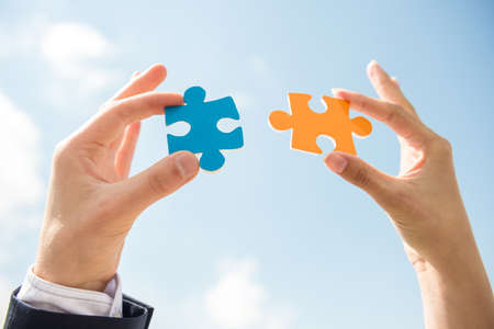 Photo for Closeup of business people wanting to put two pieces of puzzle together. Sky background. - Royalty Free Image