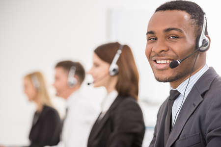 Photo pour Group of agents sitting in line in a bright call centre. - image libre de droit