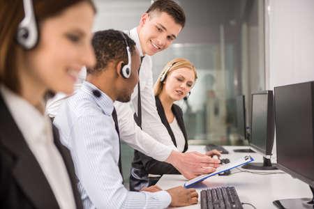 Foto de Manager explaining something to his employee in a call centre. - Imagen libre de derechos