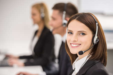 Photo pour Smiling beautiful lady working at call center with colleagues in office. - image libre de droit