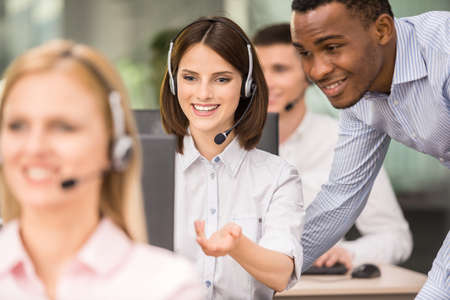 Photo pour Manager explaining something to his employee in a call centre. - image libre de droit
