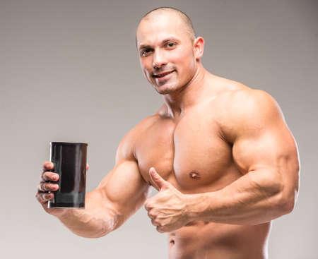 Photo pour Muscular bodybuilder drinking protein on a dark background. - image libre de droit