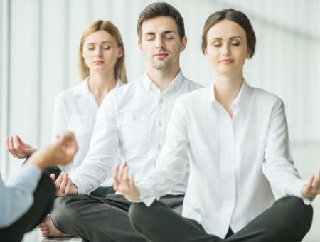 Foto de Tired business people sitting in yoga pose at office. - Imagen libre de derechos