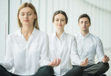 Photo pour Coworkers meditating at office, taking break with their eyes closed. - image libre de droit