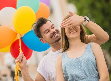 Foto de Handsome man surprising his girlfriend with colorful balloons. Romantic date outdoors. - Imagen libre de derechos