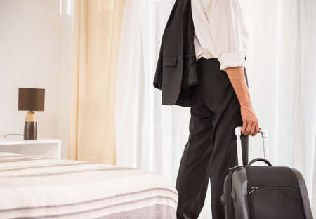 Photo for Businessman with his suitcase at the hotel room. Back view. Close-up. - Royalty Free Image