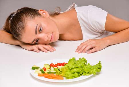 Photo pour Young sad woman with a plate of salad. - image libre de droit