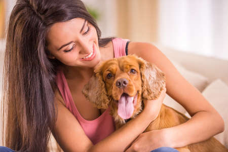 Happy young woman with dog are sitting on sofa.