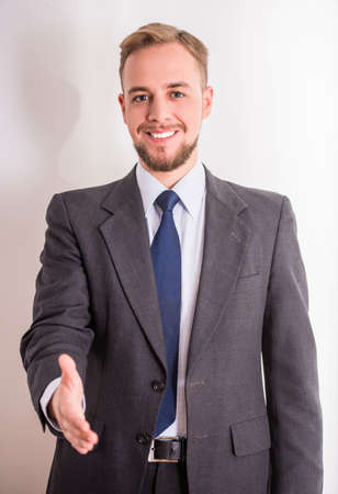 Handshake. Portrait of a young cheerful businessman holding hand for shaking