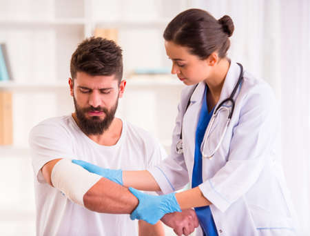 Foto de Injury hands. Young man with injured hands. Young woman doctor helps the patient - Imagen libre de derechos